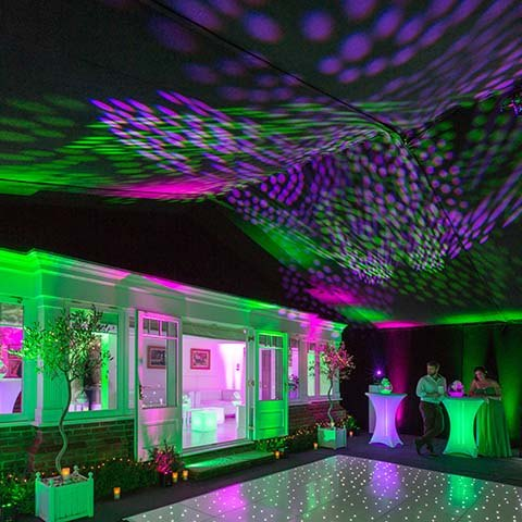 Marquee house extension for a 50th birthday party pink and green lights