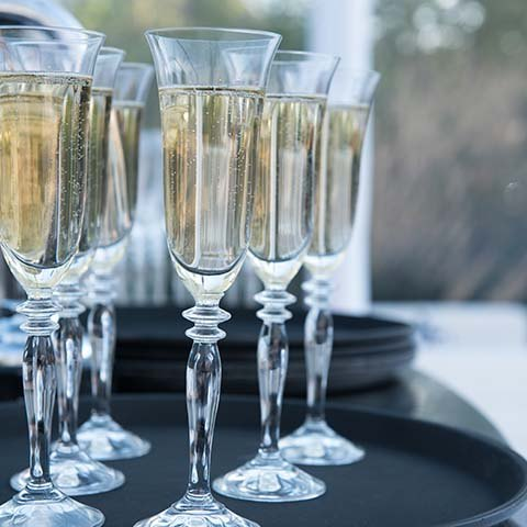 Sparkling wine champagne in tall glass flutes on tray