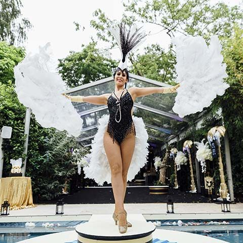 Gatsby dancer in full costume with feathers on a podium on top of a bespoke pool